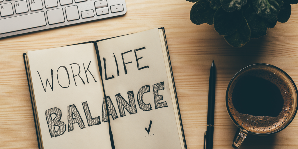 """Handwritten words """"Work/Life Balance"""" in an open notebook with a pen, and a cup of coffee"""